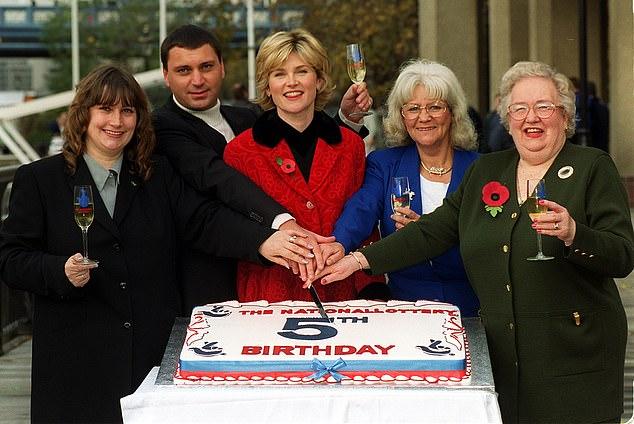 Presenter Lotere Nasional Anthea Turner (tengah) bergabung dengan para pemenang jackpot sebelumnya untuk merayakan ulang tahun kelima permainan tersebut pada hari Minggu 14 November 1999. Dari kiri: Elaine Thompson, yang meraih 2,7 juta pada tahun 1995; Gary Ashmore, pemenang 1,6m pada 1997; Anthea Turner; Penny Haigh, yang menang 1,3m pada tahun 1996; dan Marjorie Longdin, bibi dari pemimpin Konservatif William Hague, yang memenangkan £ 856.000, pada tahun 1998